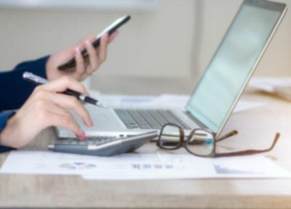 Hände einer Person am Laptop mit Handy und Stift in der Hand