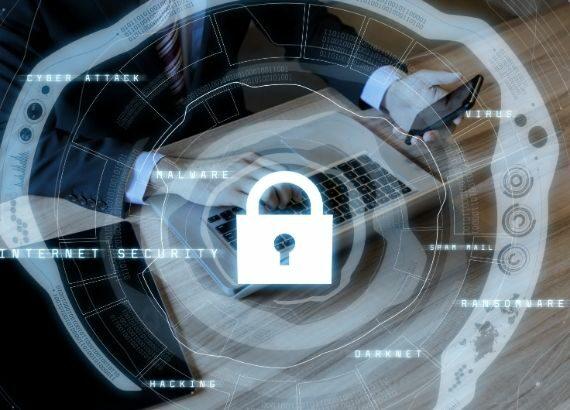 Symbolbild für IT-Sicherheit; im Hintergrund eine Person mit Laptop und Handy, im Vordergrund ein geschlossenes Schloss